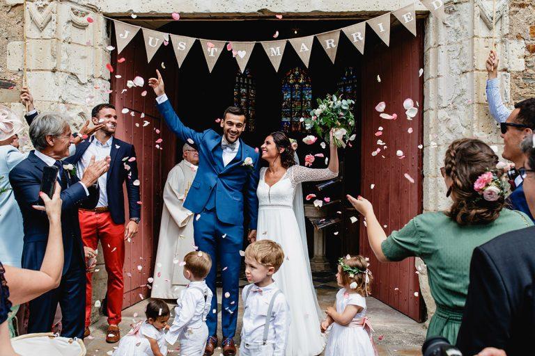 Les mariés sortent de l'église de Brissac Quincé par Jérémy FIori photographe de mariage à Angers