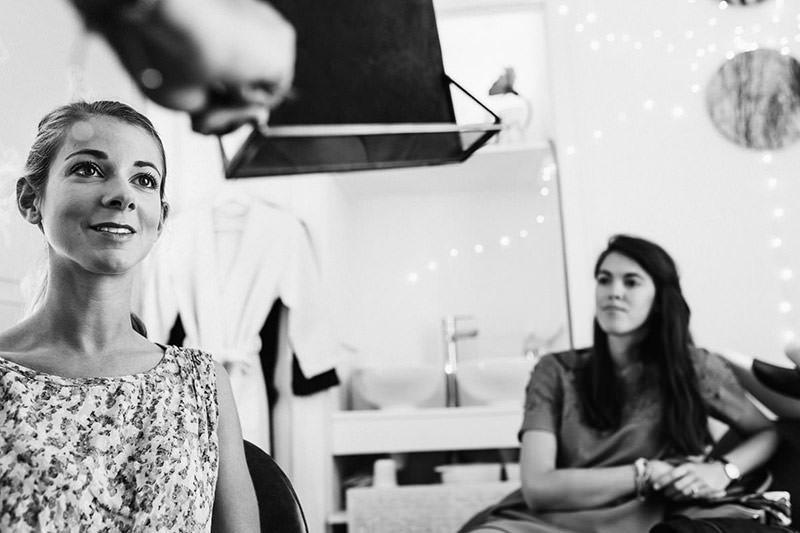 La mariée regarde son maquillage de mariage dans un salon de coiffure à Nantes - Photo : Jérémy Fiori photographe de mariage à Angers