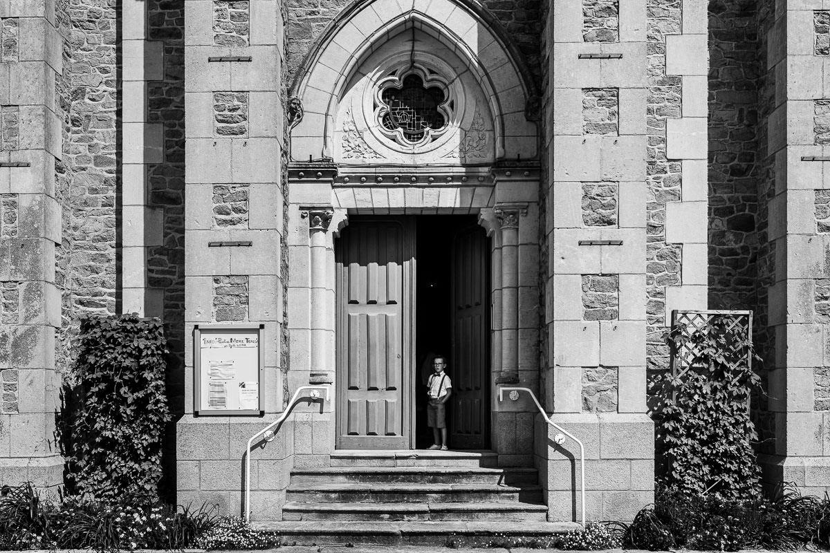 Un enfant seul devant la porte de l'église des Sorinières - Photo : Jérémy Fiori photographe de mariage à Angers