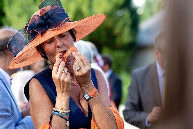 Une femme invitée au château de la Pigossière pour un mariage joue avec des crevettes - Photo : Jérémy Fiori photographe de mariage à Angers