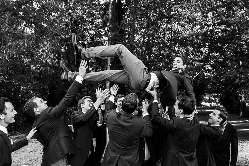 Le marié est projeté en l'air par les invités au château de la Pigossière - Photo : Jérémy Fiori photographe de mariage à Angers