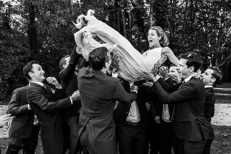 Les invités lancent la mariée en l'air dans le parc du château de la Pigossière - Photo : Jérémy Fiori photographe de mariage à Angers