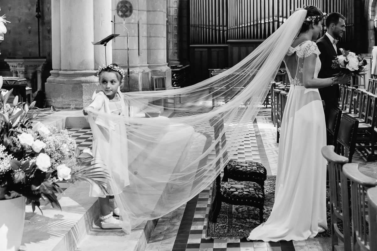 Une enfant d'honneur tient le voile de la mariée - Photo : Jérémy Fiori photographe de mariage