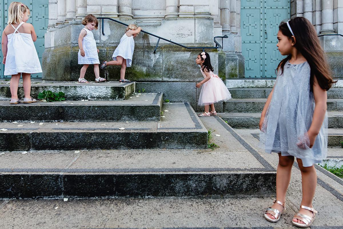 Des petites filles jouent sur les marches de l'église Saint Laud - Photo : Jérémy Fiori photographe de mariage à Angers