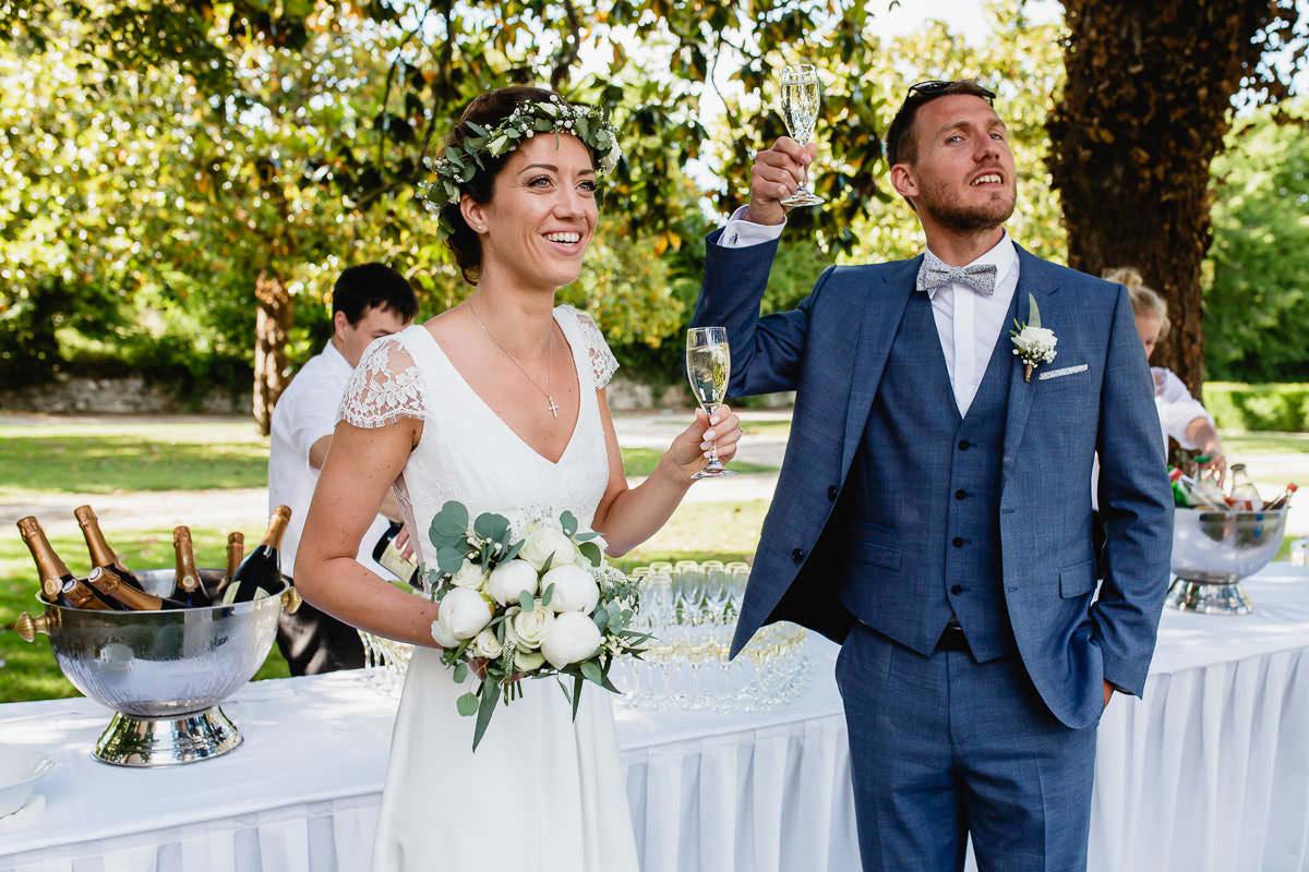Les mariés invitent leurs proches à venir se servir au cocktail dans le parc du château de la Perrière - Photo : Jérémy Fiori photographe de mariage